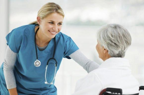 Beautiful yoSenac Caruaru curso técnico em enfermagem 2016 (imagem ilustrativa)ung female doctor talking to an elderly patient in a wheelchair. Horizontal shot.