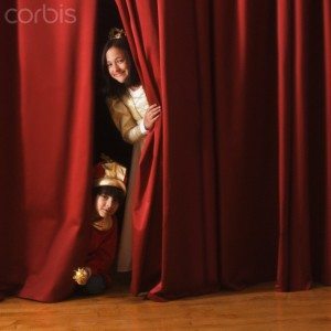 Kids peeking out from behind stage curtains