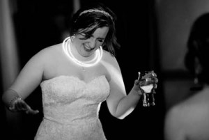 Missy on her wedding day smiling and holding a glass of wine