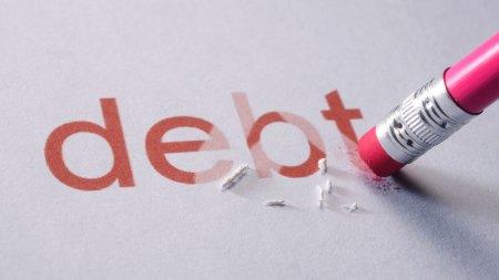 The word debt being erased by a pencil eraser