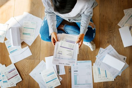woman struggling with bills while sitting on a wooden floor