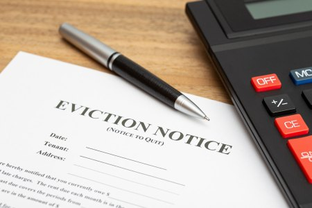 home eviction notice underneath a calculator and pen