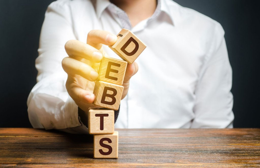 man's hand knocking over a stack of blocks that spell debt