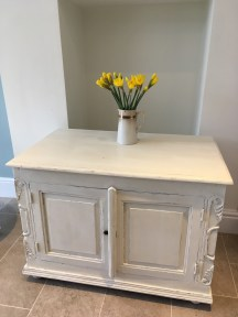 Large antique cabinet painted in Old White with distressed finish.