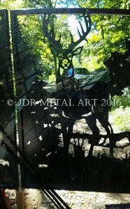Picture of ornamental deer style driveway gate taken from inside skid steer..