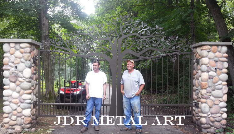 These are custom built driveway gates that were plasma cut by jdr metal art. They are mounted to stone columns and have a plasma cut metal art tree design.