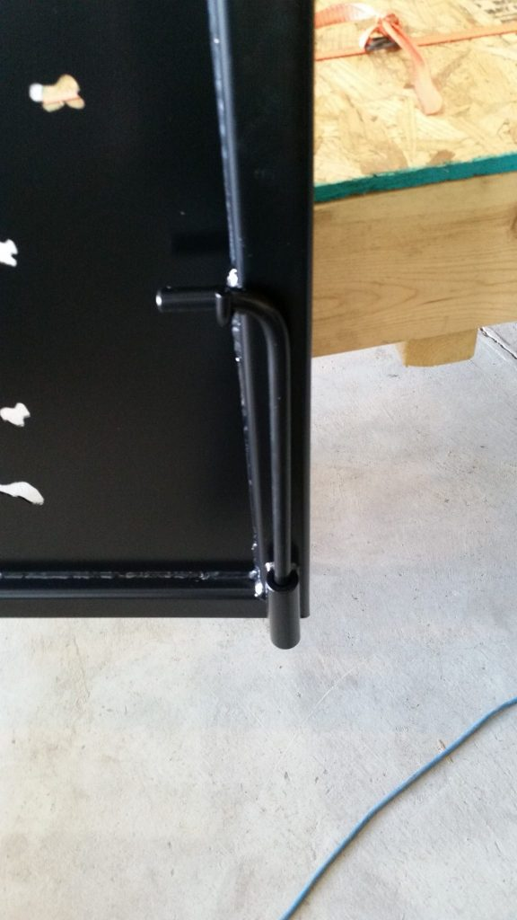 A drop pin welded to the back of a black powder coated gate.