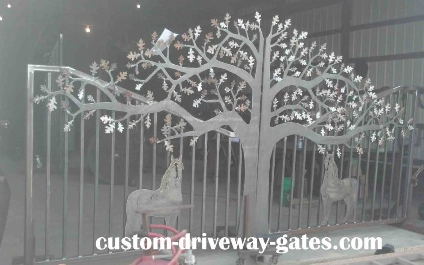 Rustic California driveway gates with tree and horse design.