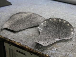 Nachdem Nietenhalter eingesetzt sind, werden Schale und das grob zurechtgeschnittene Polster mit Kleber eingesprüht
