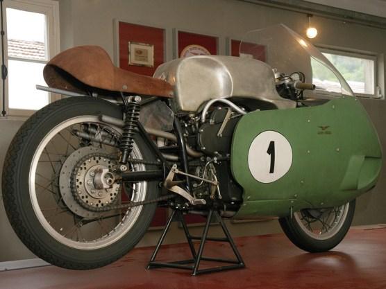 Die V8-Rennmaschine und ein zweiter Motor stehen im Werksmuseum. Eng geht's zu mit acht Vergasern, Auspuffrohren und vier obenliegenden, über ein zentrales Zahnrad angetriebenen Nockenwellen