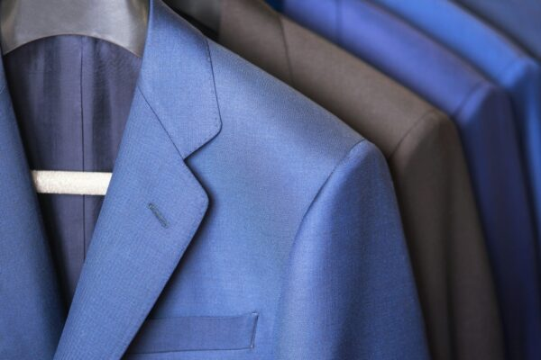 close-up-luxurious-style-gentlemen-suit-row-hanging-closet