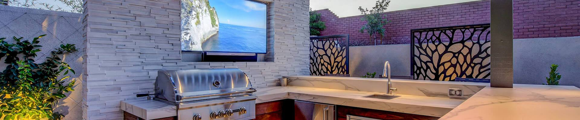 Dusk Photography of Custom Outdoor Kitchen and Outdoor Living Area with a Media Wall, and Patio by Custom Outdoor Living of Las Vegas, Nevada