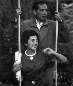 Fotografía en blanco y negro de Miguel Delibes detrás de una mujer sentada en un columpio