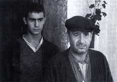 Fotografía en blanco y negro de un hombre con boina y un joven detrás.