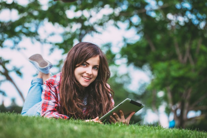 Connected. Woman lying on green grass with tablet in the park.