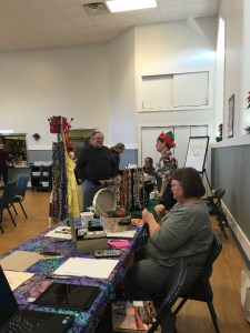 Person staffing a table and knitting at the Alternative Gift Market for justice