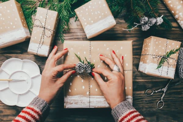Woman?s hands wrapping Christmas presents on brown paper decorated with painted snow, fir branches and pinecones on a rustic wooden board. Top view (Woman?s hands wrapping Christmas presents on brown paper decorated with painted snow, fir branches a