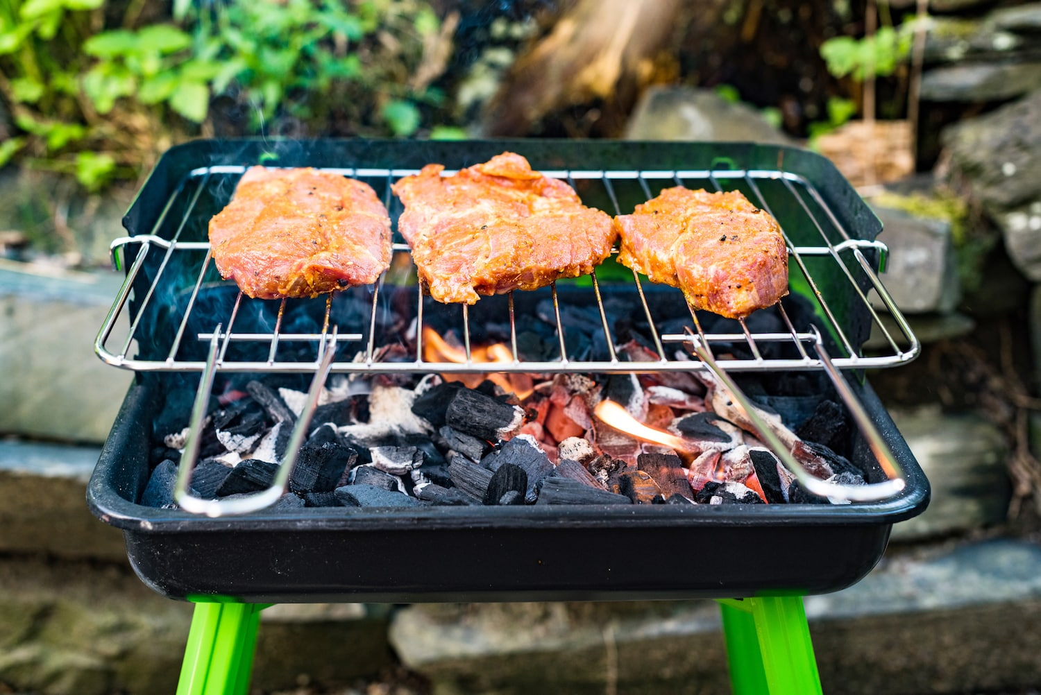 steaks on charcoal barbecue with flames