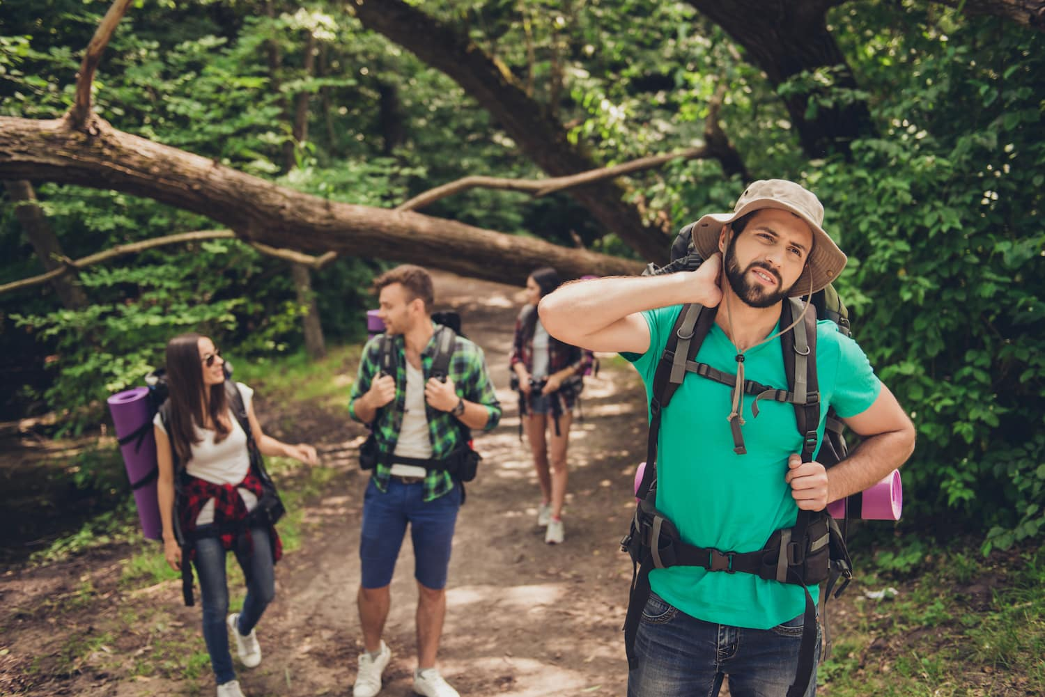 Hard, difficult, tiring and exhausting expedition of four friends in wild forest in trail. Guy is struggling of a neck pain, massaging it (Hard, difficult, tiring and exhausting expedition of four friends in wild forest in trail. Guy is struggling of