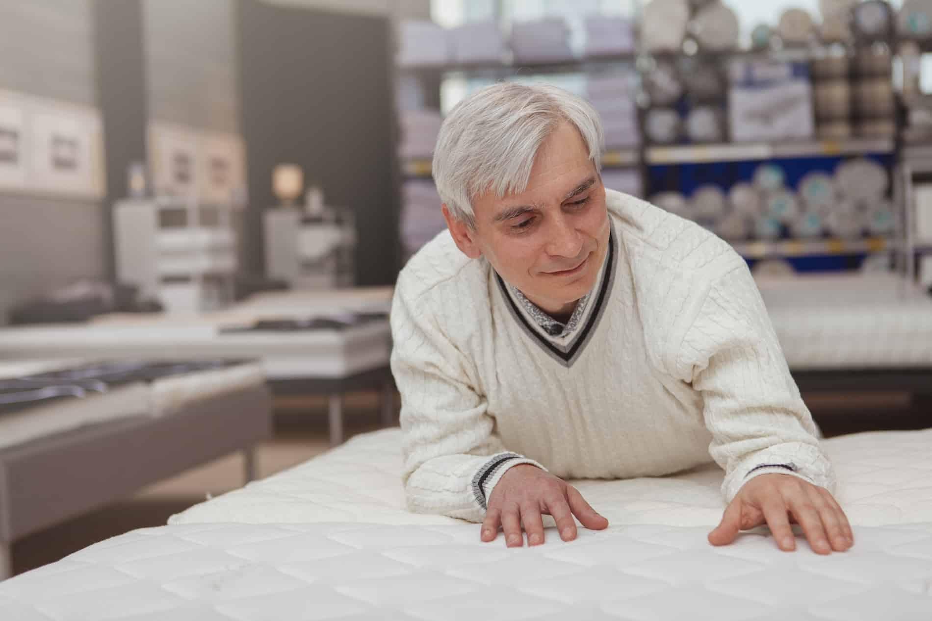 Senior man lying on orthopedic mattress at furniture store, copy space. Elderly male customer choosing new comfortable orthopedic bed at home goods store. Healthy sleep concept (Senior man lying on orthopedic mattress at furniture store, copy space. E