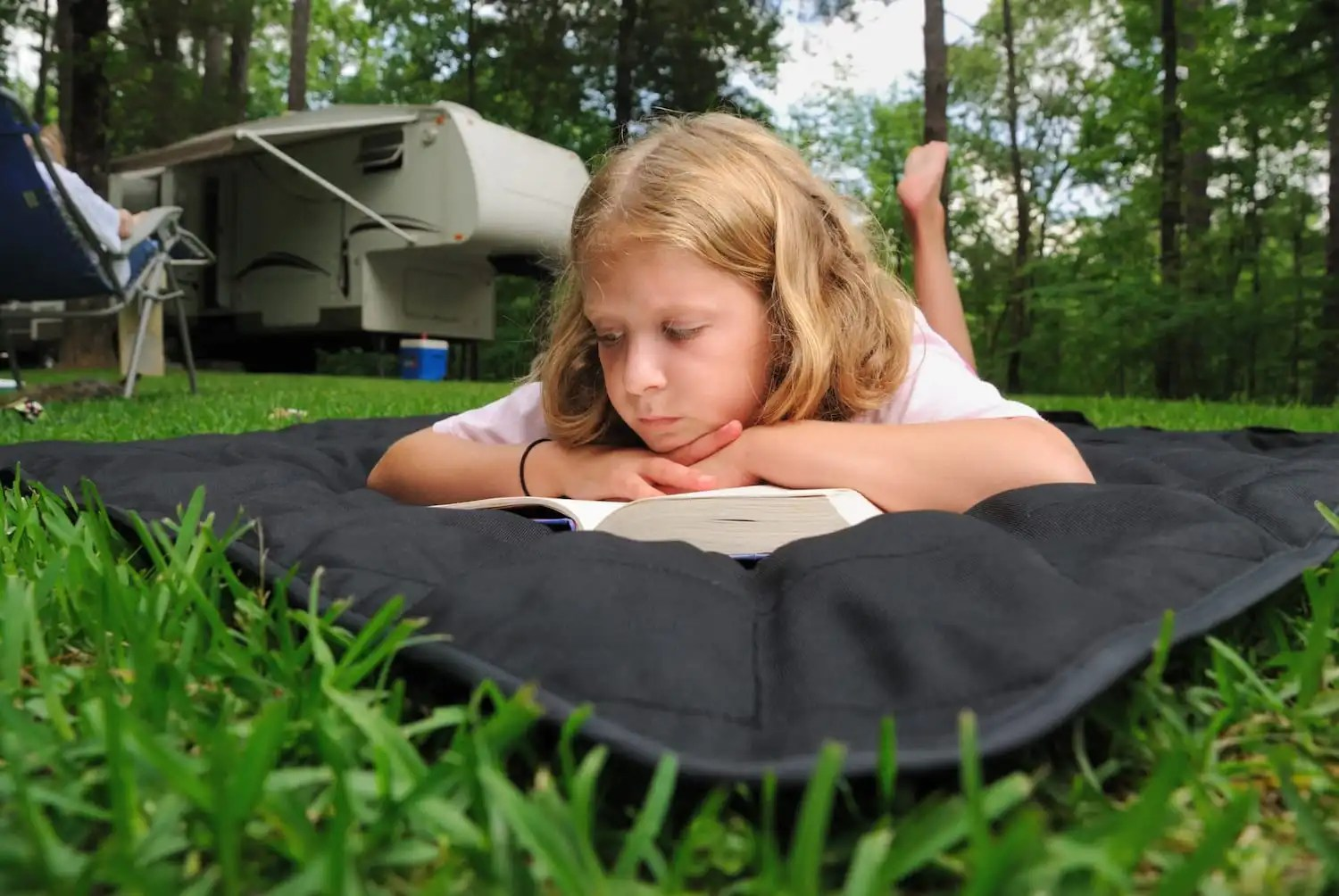 Young girl studying at a campsite