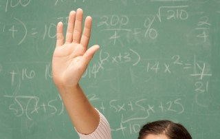 A student's hand raised in front of a chalk board