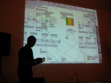 Antony Hall demonstrates the m-Log in front of a projection of a deliriously rhizomatic interface
