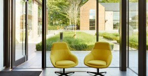 Landscape visible through glazed entrance. Yellow chairs in front of doorway.