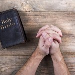 Bible and praying hands