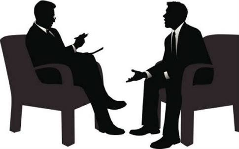 two men sitting down at an interview section
