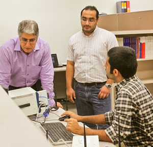 ECE Professor Marwan Krunz (left) and doctors students analyze wireless transmission signals in the lab