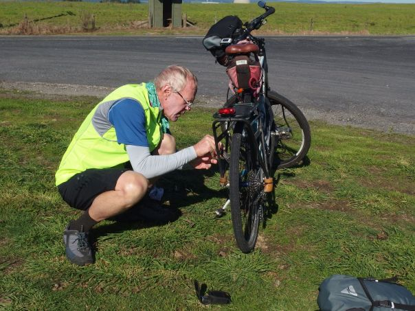 Eric pulling a tiny rock out of the disk brake pad near Lake Taupo, NZ.