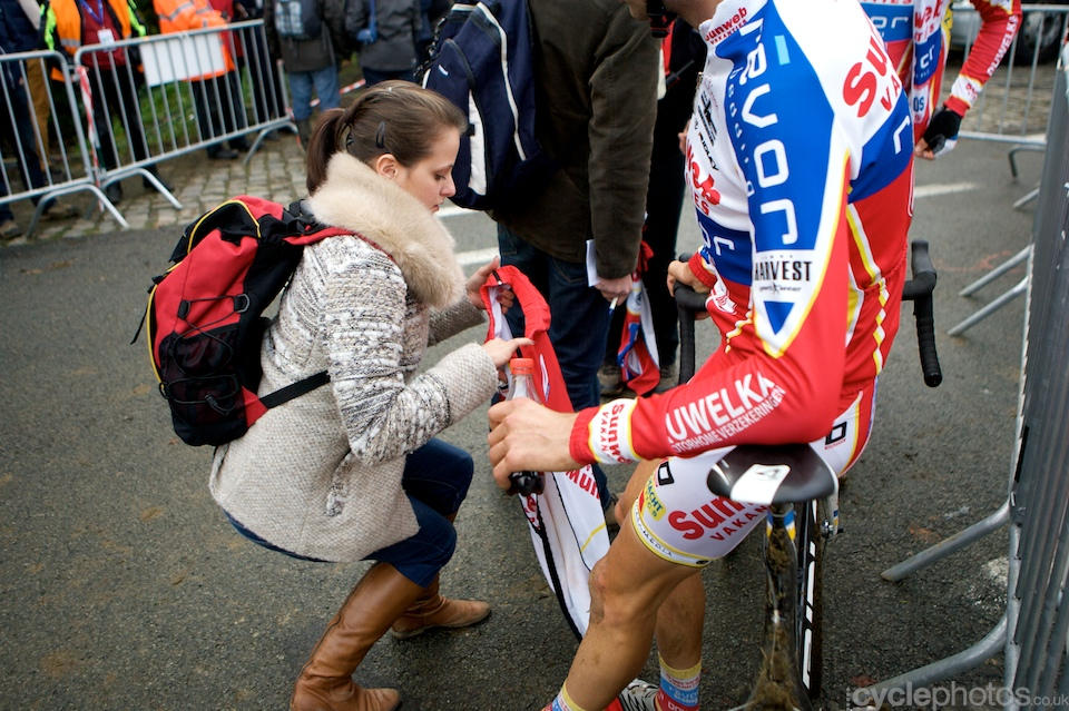 Vinnie Braet's girlfriend helps on the tracksuit bottom after the first round of the Bpost Trofee cyclocross race in Ronse, Belgium.