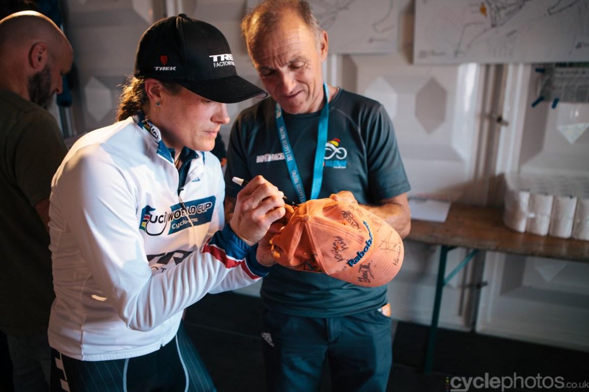 Katie Compton signs a baseball cap, held by Rudy de Bie, captain of the Belgian national team.