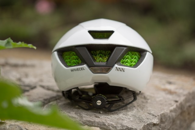 rear view of a white road bike helmet sitting on a stone planter with out of focus plants nearby.