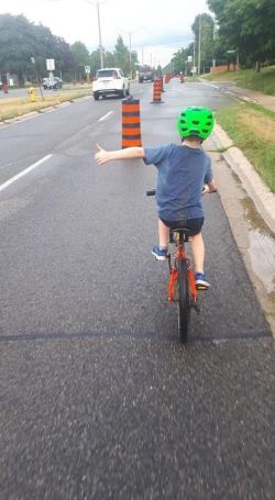 A school-aged child enjoying the temporary bike lanes, as evidenced by a big thumbs up as they ride past the large orange and black construction cones.