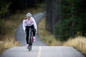 She is riding a road bike and wearing warm clothing.