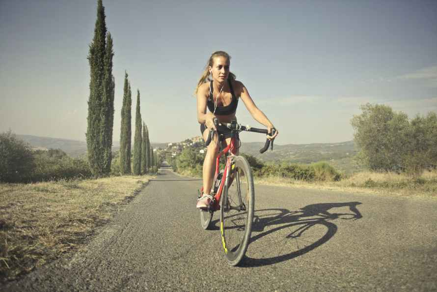 woman in black tank top riding on bicycle on road