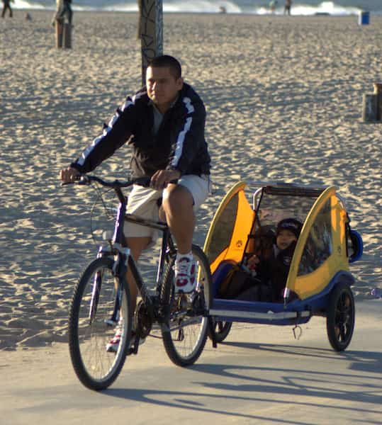 Father on bike, son in bike buggy