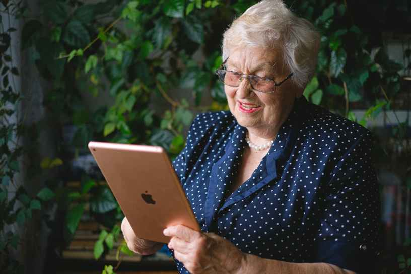 elderly happy woman making video call online on modern tablet