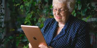 elderly happy woman making video call online on modern tablet