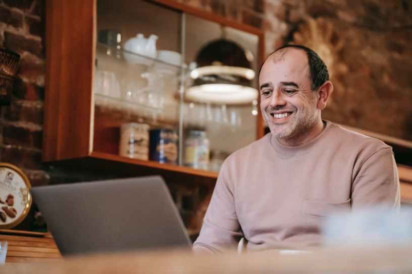 positive ethnic man smiling while working remotely on laptop in apartment