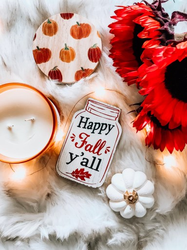 wooden cutout mason jar that says 'happy fall yall', orange sunflowers, pumpkin scented candle, white pumpkin, fur blanket, 50+ fall content ideas