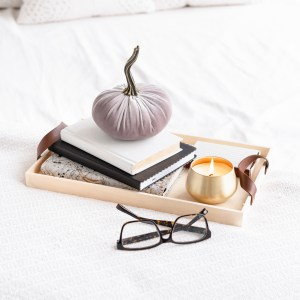 tray with a stack of books, decorative pumpkin. burning candle. reading glasses.