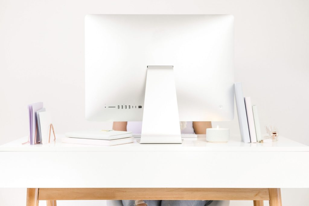 girl sitting behind desktop computer, books and candle ontop of desk. White desk, pastel colours, ripped jeans.