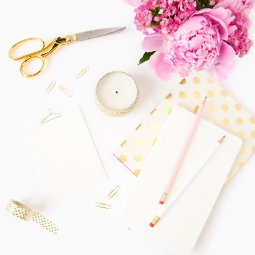 pink, gold and white flat lay. candle, paperclips, scissors, washi tape, paper, folders, pencils, pink peopnies. Resources for any blogger of any niche.