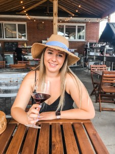 Scheuermann Winery west port. red wine. girl with hat and blue ribbon around it. wine babes of ottawa.