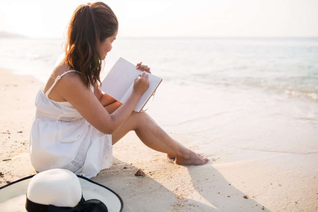 girl sitting in the sand, writing in a book. white dress, white hat. beach background. how to become the best version of yourself.