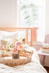 flowers sitting on tray on top of bed.