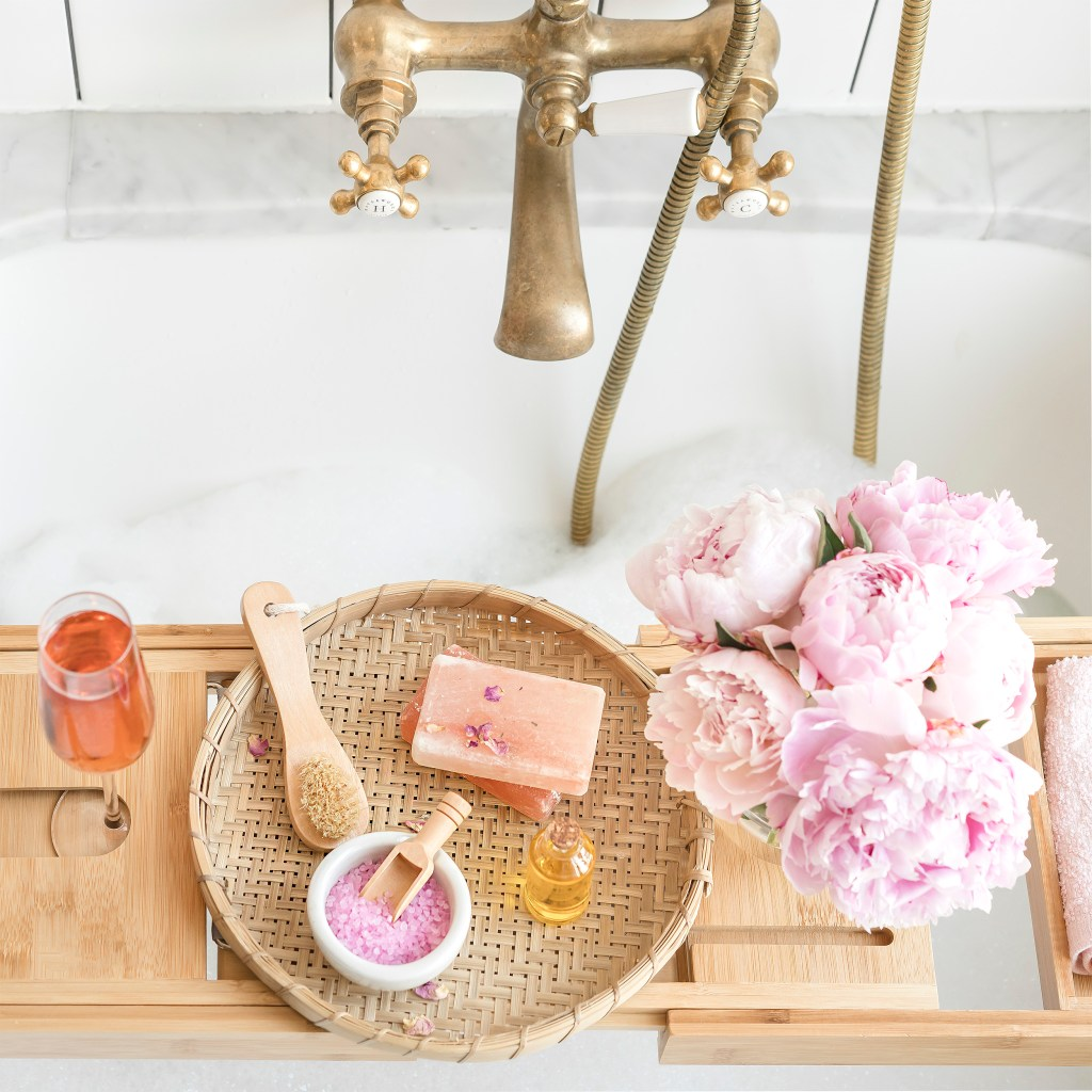 bathtub with gold faucet. bath tray with flowers, rose wine, tray, bath scrubbing salts and soap. 50 free self-care ideas